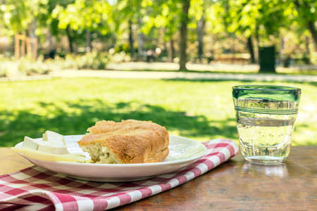 Summer picnic in a park with bread and cheese