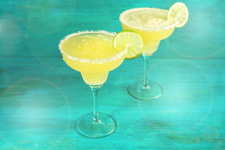 Lemon Margarita cocktails on vibrant teal with copyspace Stock Photo