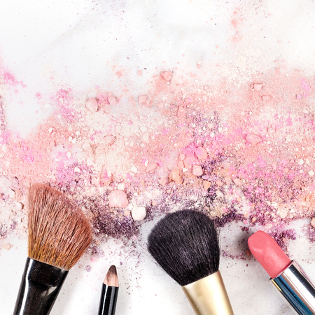 Makeup brushes, lipstick and pencil with powder and copyspace