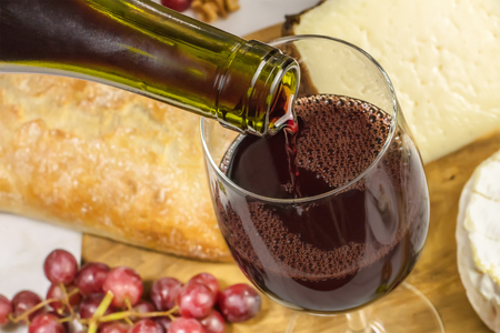 Closeup of red wine poured into glass at tasting Stockfoto