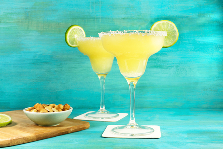 lemon wedge: Margarita cocktail photo on vibrant background with copyspace