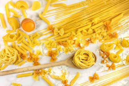 rotini: Various types of pasta on marble with flour