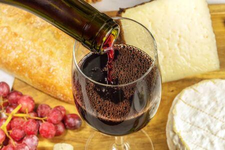 Close-up van rode wijn gegoten in glas bij proeven Stockfoto
