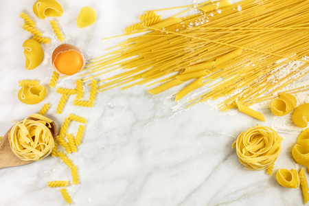 rotini: Various types of pasta on marble with egg and copyspace