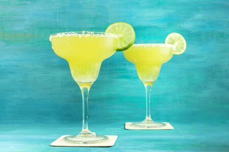 lemon wedge: Lemon Margarita cocktails on vibrant turquoise with copyspace