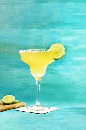 lemon wedge: Lemon Margarita cocktail on vibrant turquoise with copyspace Stock Photo