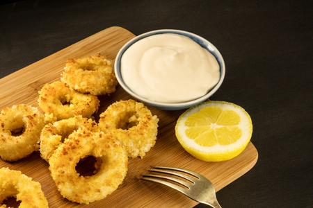 lemon wedge: Closeup of calamari rings with aioli sauce and copyspace