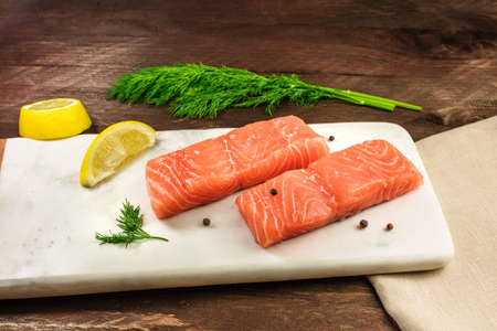 lemon wedge: Two slices of salmon on dark background with copyspace