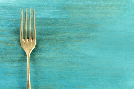 Vintage fork on vibrant turquoise with copyspace