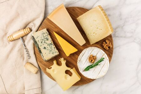 stilton: Selection of cheeses with corkscrew, cork, and copyspace Stock Photo