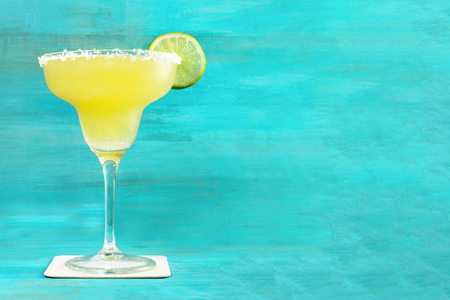 Lemon Margarita cocktail on vibrant turquoise with copyspace Stock Photo