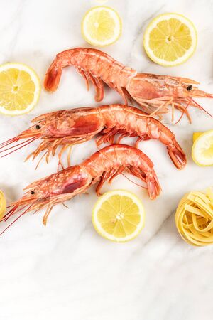 Raw shrimps with lemon and pasta on marble table