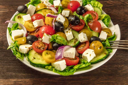 onion rings: Greek salad with feta, fresh vegetables, and copyspace