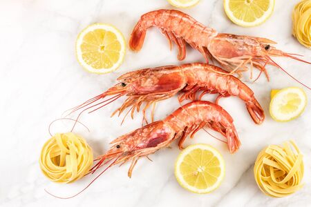 lemon wedge: Raw shrimps with lemon and pasta on marble table