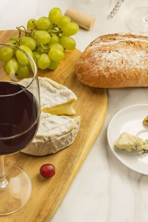 stilton: Glass of red wine with cheeses, grapes, and copy space