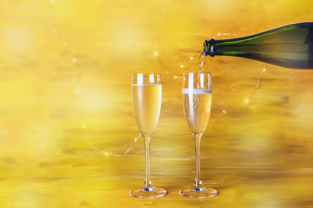 Champagne poured into glasses on golden background