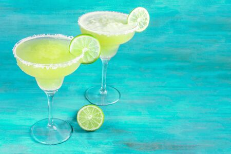 Lemon Margaritas on vibrant blue with copy space, toned