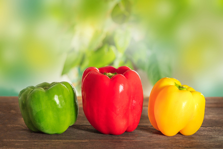 Vibrant bell peppers on blurred natural background with copyspac
