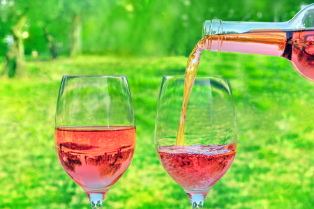 Rose wine poured from bottle into glasses at picnic Stock Photo