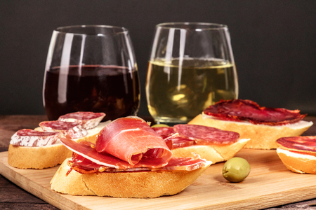 Spanish embutidos tapas, sandwiches with sausages, and wine