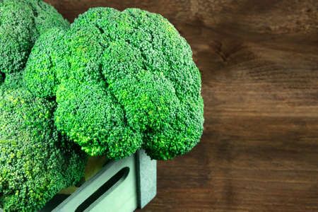 Broccoli heads in crate on rustic texture with copyspace
