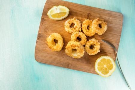 Calamari rings with lemon and copy space, overhead shot