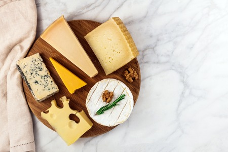Selection of cheeses on white marble table with copyspace
