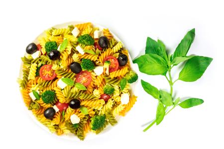 Plaat van deegwarensalade met basilicumbladeren op wit Stockfoto