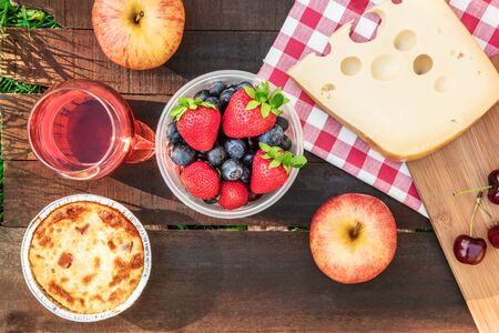 Picnic food and rose wine on wooden board with copyspace Stock Photo