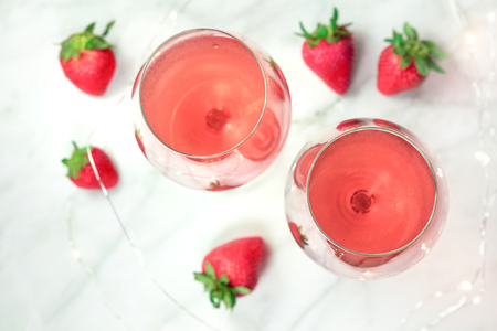 Overhead photo of two glasses of rose wine with strawberries Stockfoto