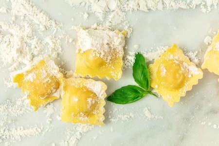 Overhead photo of ravioli with flour and basil leaves