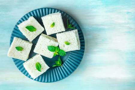 Plate of cucumber sandwiches shot from above with copyspace
