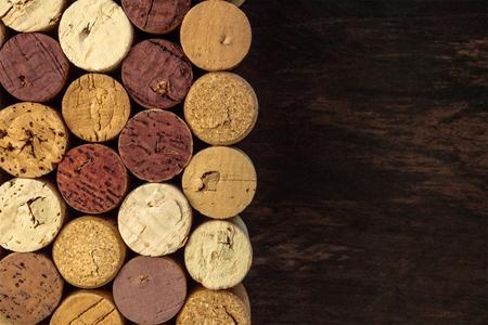 Wine corks on dark wooden texture with copyspace Archivio Fotografico