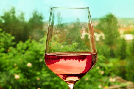 Enoutourism. Glass of rose wine in front of European village