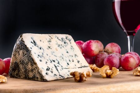 Blue cheese, grapes, and wine on black with copyspace