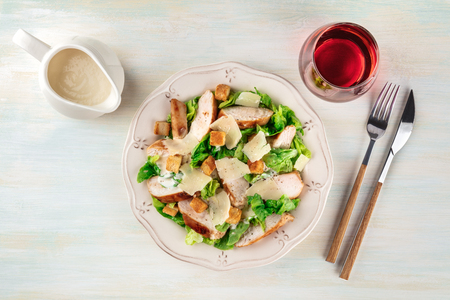 Chicken Caesar salad on light background with wine