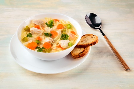 Chicken soup with noodles, bread, and copy space