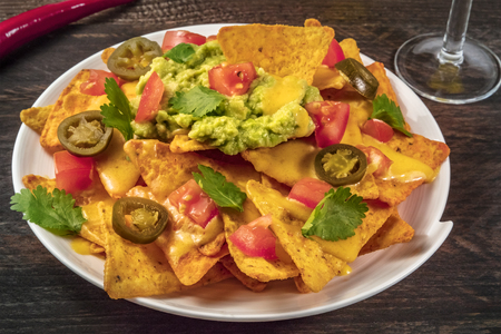 Nachos with cheese, traditional Mexican snack, on rustic backgro Stock Photo