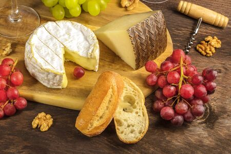 Cheese, grapes, and corkscrew on rustic texture Stock Photo