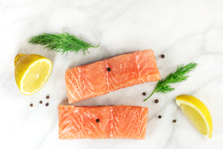 Slices of salmon on white with lemons, dill, and copyspace Imagens