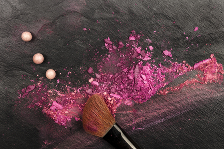 Closeup of makeup brush with eye shadows on black with copy space