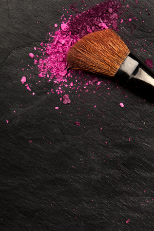 Closeup of makeup brush with eye shadow on black with place for text