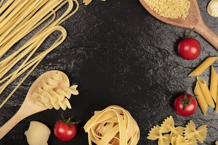 Overhead photo of different types of pasta with cherry tomatoes on black