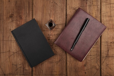 A black book, a leather journal, and ink well and pen