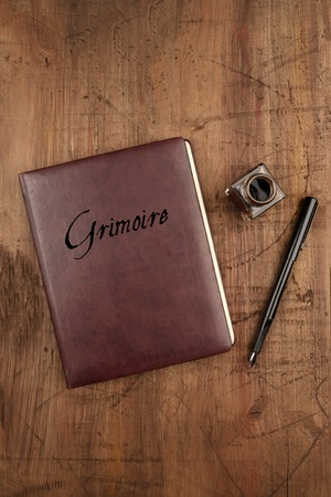 Leather bound journal titled Grimoire, and ink well and pen Standard-Bild