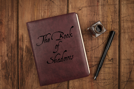 Leather bound journal titled The Book of Shadows, a witchs grimoire, and ink well and pen