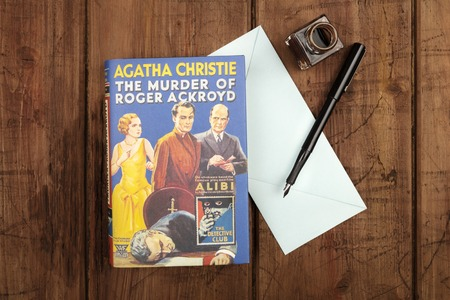 The Murder of Roger Ackroyd, detective novel by Agatha Christie, with blue envelope, and ink pen and well Editorial