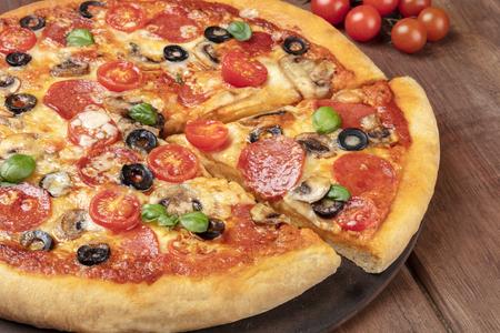 Pepperoni pizza on a pizza stone, closeup of a slice Archivio Fotografico - 105015982