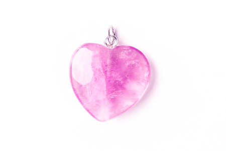 Overhead photo of a pink crystal heart on a white background with copy space