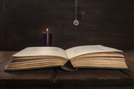 An open old book on a dark background with a burning candle, a pentacle, and copy space